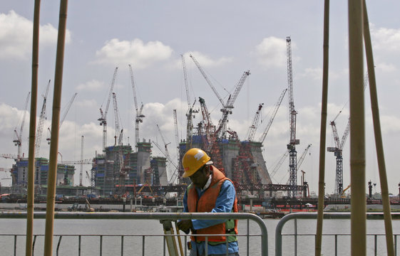 A construction worker keeps his equipment as the Marina Bay Sands Resort construction site is seen in the background in Singapore