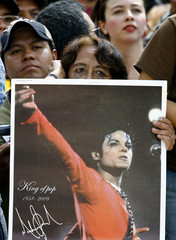 A woman holds up a picture of Michael Jackson in Mexico City