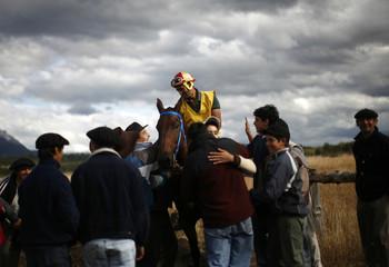 """Residents congratulate a jockey who won a race at the """"Fiesta del Lenador"""" in Mallin Ahogado"""