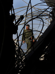 PALESTINIAN POLICEMAN SEARCHES NAVAL POST AFTER ISRAELI AIRSTRIKES.