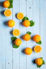 Fresh orange with leaves on wooden background. Top view,