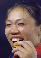 TANG LIN OF CHINA BITES HER OLYMPIC GOLD MEDAL ON THE PODIUM IN THE WOMEN'S JUDO UNDER 78KG FINAL.