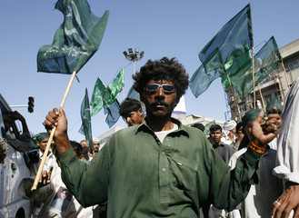 Activist from Pakistan Muslim League holds flags during a rally to mark Labour Day in Karachi