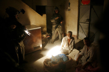 An Iraqi family sits on the floor as U.S. soldiers search their house for weapons in the town of Al-Meshahda