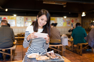 Woman taking photo with cellphone on seafood barbecue