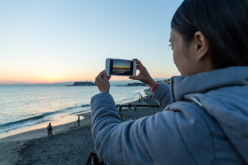 Woman taking photo in Shonan of Japan