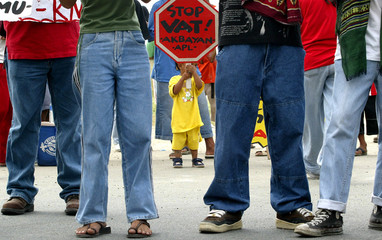 A Filipino child holds a sign among activists opposing the approval of the newly raised ...