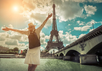 Woman tourist selfie near the Eiffel tower in Paris under sunlig