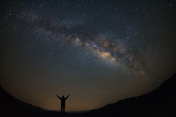 Landscape milky way galaxy with stars and silhouette of a standing happy man, Long exposure photograph, with grain.