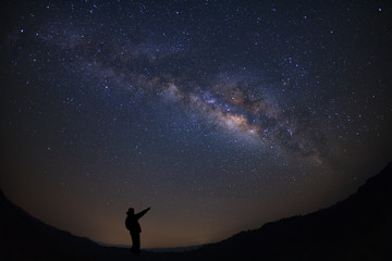 A Man is standing next to the milky way galaxy pointing on a bright star, Long exposure photograph, with grain.