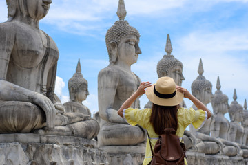 Woman tourist photographer is visiting Buddha Park in Thailand.