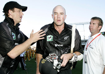 Shane Bond congratulates Peter Fulton watched by team liason Steve Addsion after New Zealand beat Australia in the second match of the Chappell-Hadlee series at Eden Park