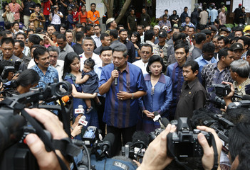 Indonesian President Yudhoyono accompanied by first lady Kristiani Yudhoyono speaks to journalists after casting his ballot in a polling station near his residence in Cikeas