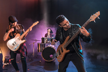 Rock and roll band with electric guitars playing hard rock music on stage