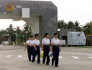 CHINESE FEMALE NAVY PERSONNEL LEAVE THE FRONT GATE OF A NAVAL BASE ON HAINAN ISLAND.