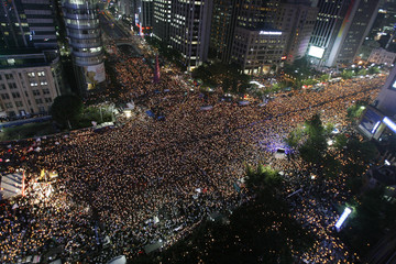 Protesters chant slogans at a candlelight vigil on a street leading to the U.S. embassy and the presidential Blue House in central Seoul