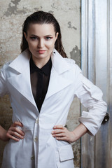 Portrait of a beautiful brunette woman with long hair posing on grunge background in white coat