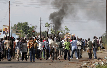 Demonstrators march along a road in the western town of Kisumu