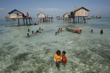 Young sea gypsies play in the water in the centre of their neighbourhood in the Sulawesi Sea in Malaysia's state of Sabah on the Borneo island
