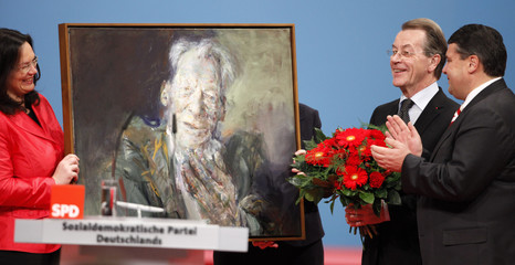 New leader of Germany's SPD Gabriel and new General Secretary Nahles present flowers and a painting to former party leader Muentefering at a party congress in Dresden