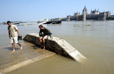 HUNGARIANS WALK ON FLOODED EMBANKMENT ROAD IN FRONT OF BUDAPEST'SPARLIAMENT.