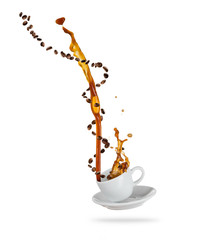 Porcelaine white cup with splashing coffee liquid with coffee beans, isolated on white background.