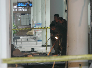 Thai policemen inspect the scene of a bomb blast at Hat Yai airport in Songkhla province, south of ...