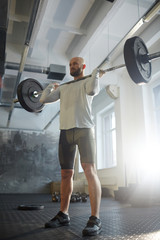 Low angle portrait of modern strongman weightlifting with heavy barbell performing shoulder press during powerlifting workout in sunlit gym