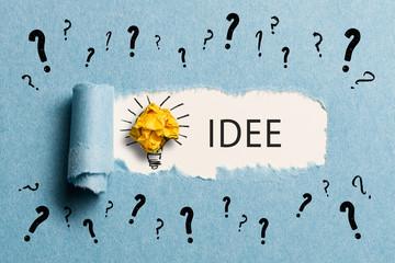 aufgerissenes Papier enthüllt Idee zu vielen Fragen