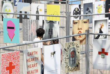 "Couple looks at posters on display at the ""Good 50x70"" exhibition at the Triennale Design Museum in Milan"