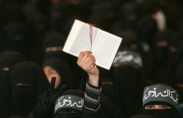 A woman holds up a copy of the Koran during a rally in Sanaa against the recent reproduction of cartoons depicting Prophet Mohammad