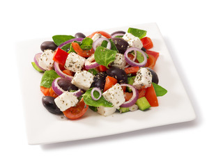 Greek salad in a square plate isolated on white