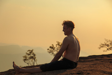 Man is engaged in physical exercises among the mountains.