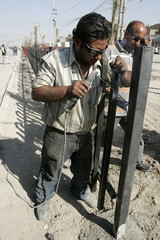 Labourers work on the construction of steel railings on a road in Baghdad