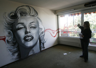 An unidentified woman takes a picture of a graffiti showing Monroe  in the former Bon Accueil Hotel in Montreux