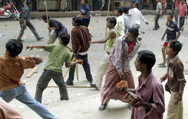 Activists throw stones at rival political activists during a clash outside an election office in Dhaka