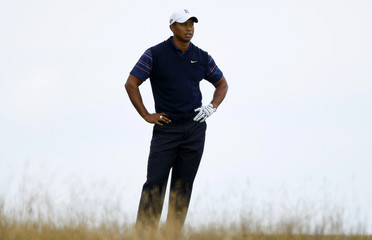 Tiger Woods of the U.S. reacts after throwing his club on the ninth hole during the first round of the British Open championship at the Turnberry Golf Club in Scotland