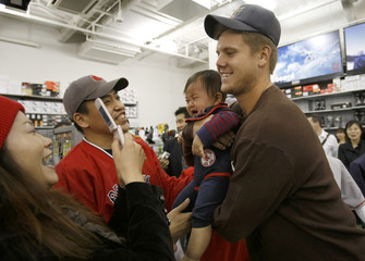 Boston Red Sox pitcher Papelbon holds a baby of a Japanese fan during a promotion event in Yokohama