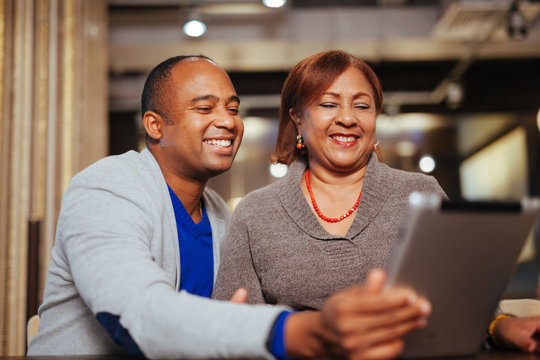 A mother and son hold a computer tablet, isolated