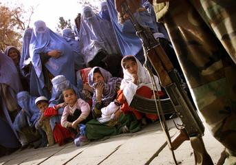 AFGHAN GUNMAN WALKS IN FRONT WOMEN WAITING FOR AID IN KABUL.