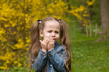 The girl has a runny nose. flowers pollen allergy. The girl is allergic to the pollen of flowers.