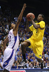 Michigan Wolverines' Harris goes for a lay--up over Kansas Jayhawks' Morris in Lawrence