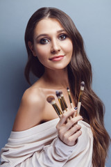 Beautiful young woman with long hair holding different make-up brushes, pastel blue background
