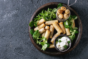 Fried spring rolls with white yogurt sauces, served in terracotta plate and fry basket with fresh green salad over black texture background. Flat lay, space. Asian food