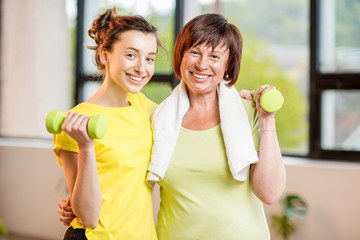Young and older women in sportswear training with dumbbells indoors on the window background