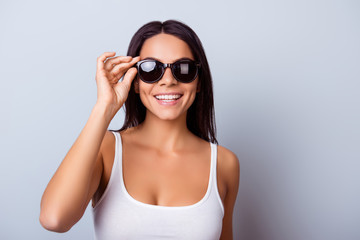 Cheerful pretty latin american lady with beaming smile in stylish spectacles is standing on the light blue background