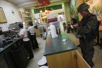 A soldier buys food at Toncontin International Aiport in Tegucigalpa