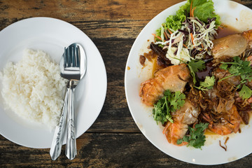 Cooked rice with a fried shrimp sauce on wooden table (wooden background)