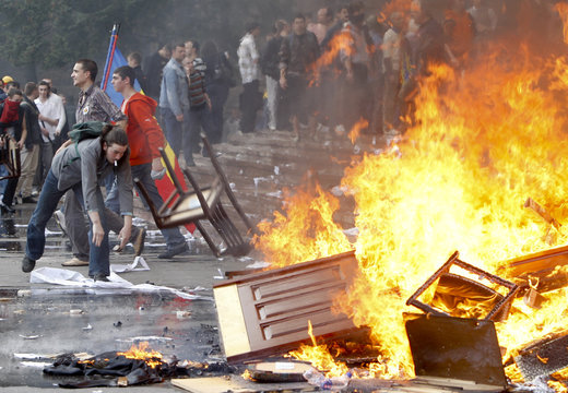 People throw furniture into a fire during a violent protest outside parliament in Chisinau