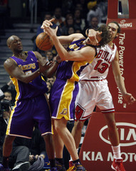 Los Angeles Lakers forward Pau Gasol loses control of the ball as he is hit by Chicago Bulls forward Joakim Noah in Chicago